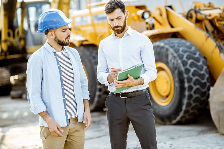 Dwie osoby rozmawiają natle maszyny budowlanej
