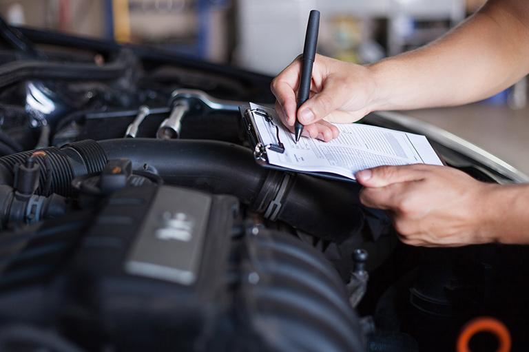 Osoba zapisuje nakarcie przy otwartej masce samochodowej