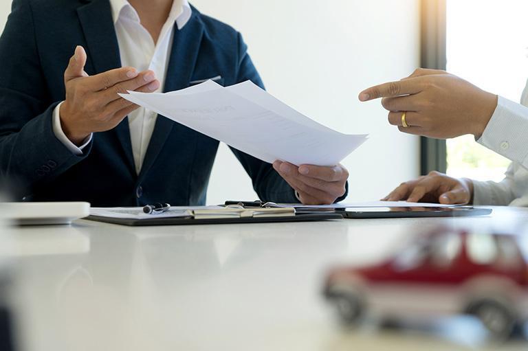 Dwie elegancko ubrane osoby rozmawiają przy stole
