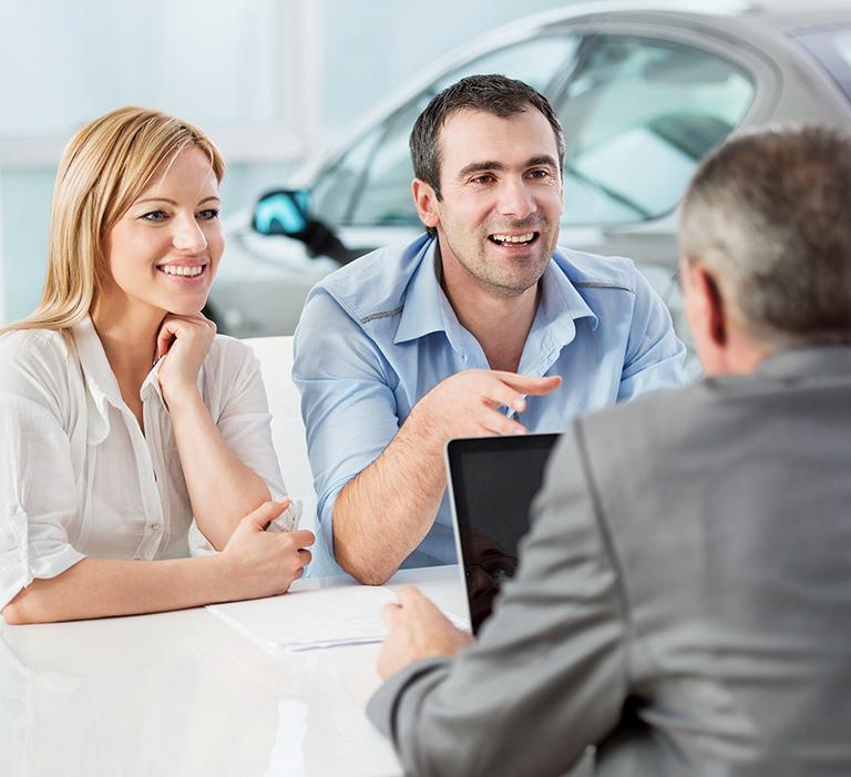 Młoda para rozmawia zosobą wgarniturze natle samochodu osobowego